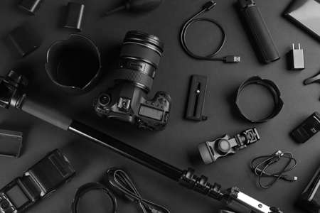 Flat lay composition with camera and video production equipment on black background