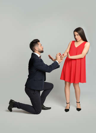Young woman rejecting engagement ring from boyfriend on light grey background