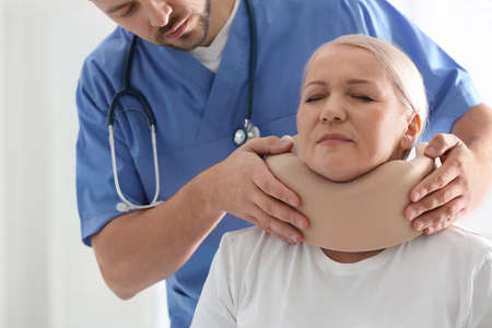 Orthopedist applying cervical collar onto patient's neck in clinic, closeup Standard-Bild