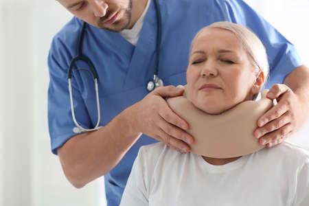 Orthopédiste appliquant un collier cervical sur le cou du patient en clinique, gros plan Banque d'images