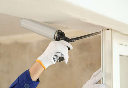 Worker using foam gun for window installation indoors, closeup