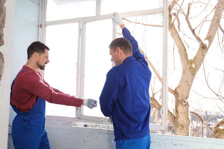 Workers dismantling old window with crowbar indoors