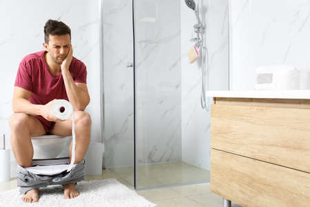 Man with paper roll suffering from stomach ache on toilet bowl in bathroom