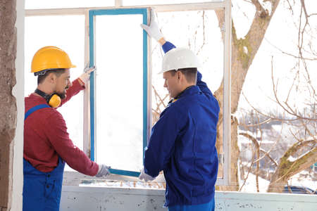 Workers in uniform dismantling old window indoors