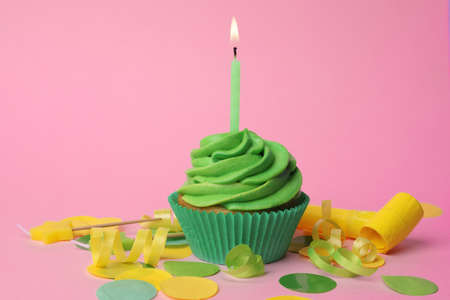 Delicious birthday cupcake with green cream and burning candle on pink background