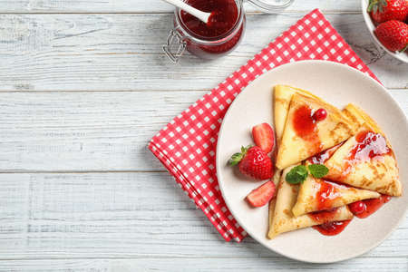 Delicious thin pancakes with strawberries and jam on white wooden table, flat lay. Space for text