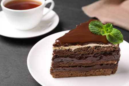 Delicious chocolate cake with mint on black table, closeup