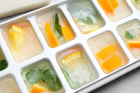 Ice cubes with orange and mint on light table, closeup Zdjęcie Seryjne