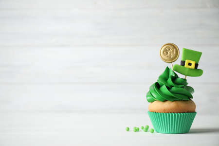 Decorated cupcake on white wooden table, space for text. St. Patrick's Day celebration