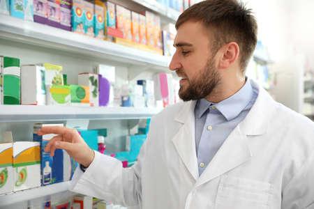 Professional pharmacist near shelves in modern drugstore Stockfoto