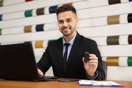 Salesman with car key at desk in office