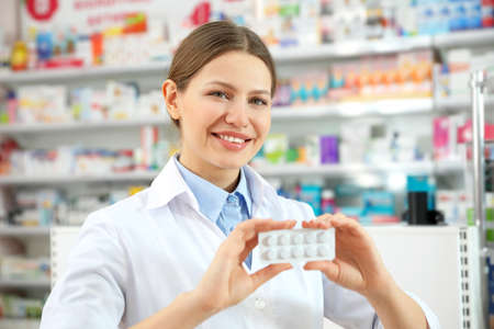 Professional pharmacist with pills in modern drugstore
