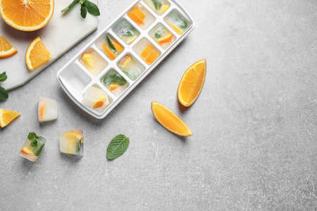 Ice cubes in tray with orange slices and mint on light grey table, flat lay
