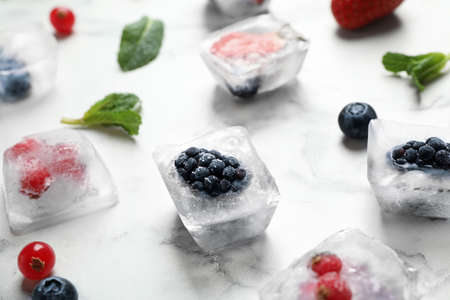 Ice cubes with different berries and mint on white marble table, closeup