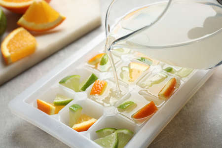 Pouring juice into ice cube tray with lime and orange on light table, closeup Zdjęcie Seryjne