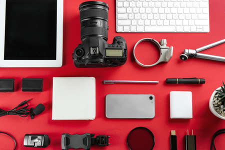 Flat lay composition with camera and video production equipment on red background Banco de Imagens