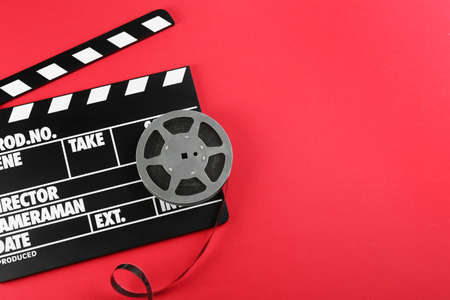 Movie clapper and reel on red background, top view. Space for text