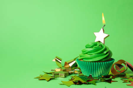 Delicious birthday cupcake with burning candle on green background. Space for text