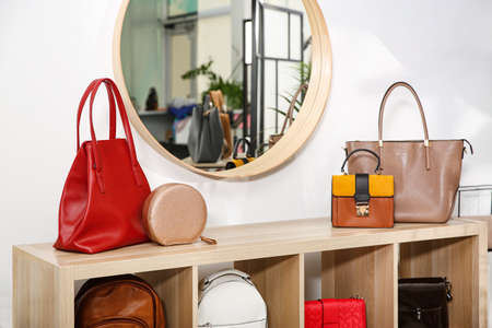 Collection of stylish woman's bags on wooden shelving unit indoors Zdjęcie Seryjne