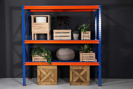 Metal shelving unit with wooden crates and different household stuff near black wall indoors Banco de Imagens