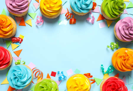 Colorful birthday cupcakes on light blue background, flat lay. Space for text 스톡 콘텐츠