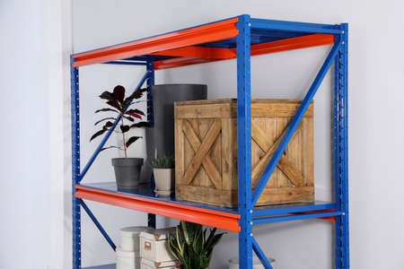 Metal shelving unit with different household stuff on light background