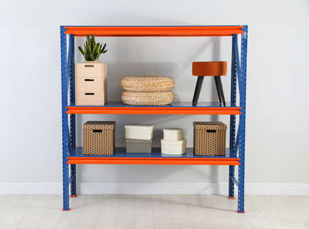 Metal shelving unit with different household stuff near light wall indoors Banco de Imagens