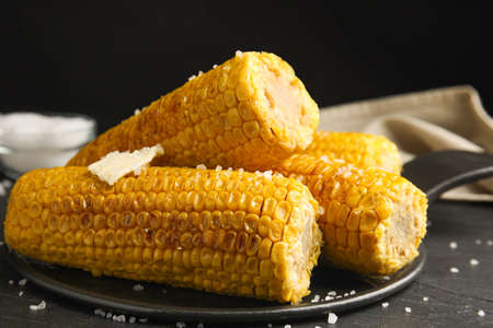 Delicious grilled corn with butter on table, closeup Stock Photo