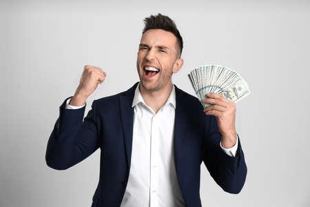 Emotional man with cash money on light grey background