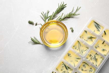 Ice cube tray with herbs frozen in oil and fresh rosemary on grey table, flat lay Archivio Fotografico