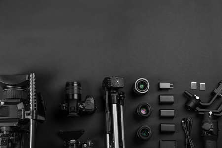 Flat lay composition with video camera and other equipment on black background. Space for text