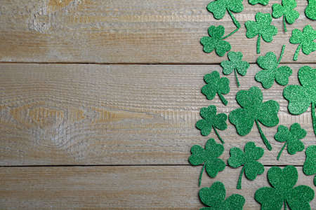 Flat lay composition with clover leaves on wooden table, space for text. St. Patrick's Day celebration
