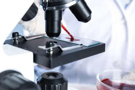 Scientist dripping blood sample onto slide on microscope in laboratory, closeup. Virus research Foto de archivo