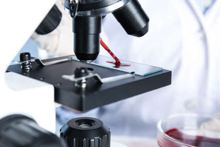 Scientist dripping blood sample onto slide on microscope in laboratory, closeup. Virus research Stock fotó