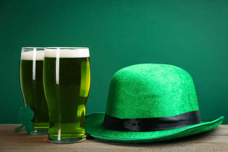 Green beer and hat on wooden table. St. Patrick's Day celebration