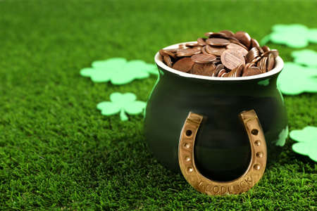 Pot of gold coins, horseshoe and clover leaves on green grass, space for text. St. Patricks Day celebration