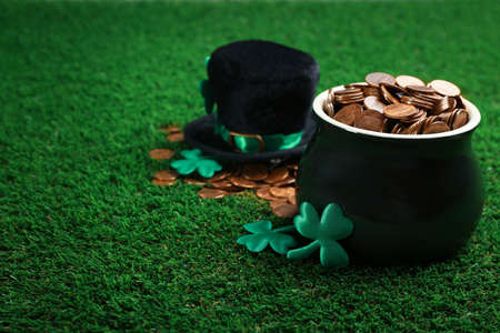 Pot of gold coins, hat and clover leaves on green grass, space for text. St. Patricks Day celebration 写真素材
