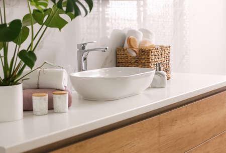 Stylish vessel sink on light countertop in modern bathroom