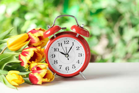Alarm clock and spring flowers on white wooden table. Time change concept