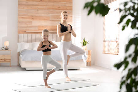 Mother and daughter in matching sportswear doing yoga together near bed at home Reklamní fotografie