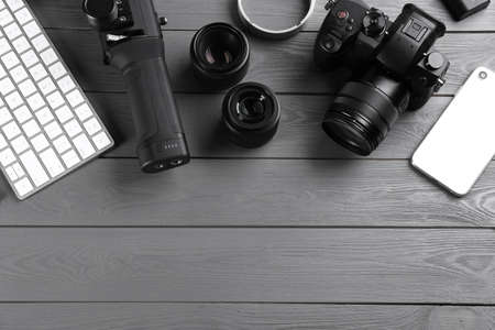 Flat lay composition with camera and video production equipment on grey wooden table. Space for text