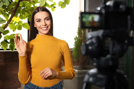 Young blogger recording video on camera indoors Stockfoto