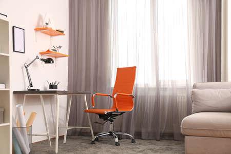 Stylish room interior with comfortable workplace near window. Design idea