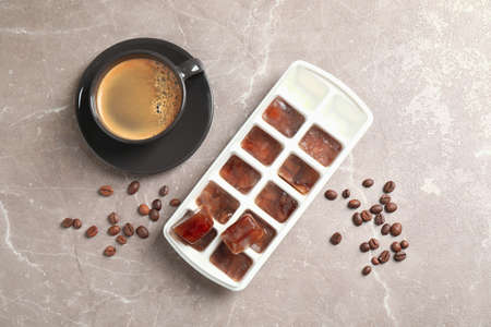 Ice cubes, cup of coffee and beans on grey table, flat lay 스톡 콘텐츠
