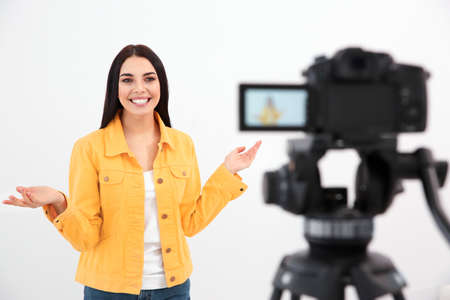 Young blogger recording video on camera against white background Stockfoto