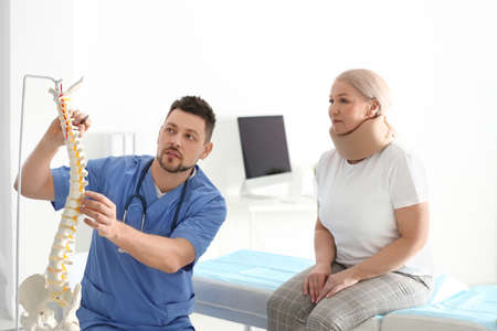 Male orthopedist explaining structure of spine to patient in clinic