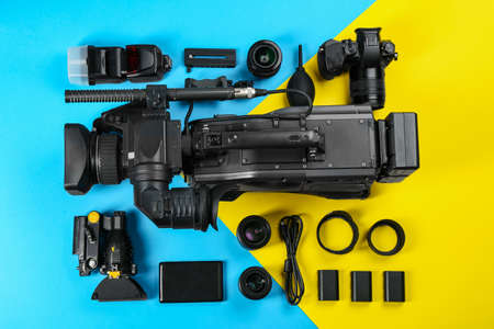 Flat lay composition with video camera and other equipment on color background