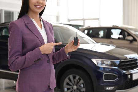 Saleswoman with key in modern car salon, closeup