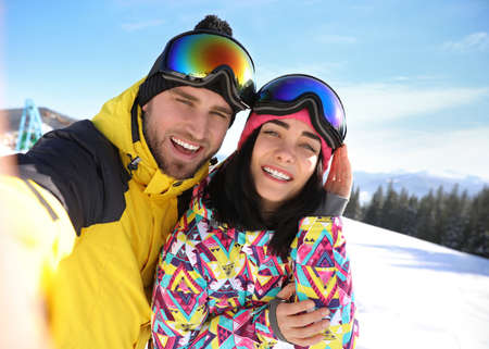 Young couple taking selfie at ski resort. Winter vacation