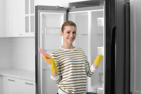 Woman in rubber gloves cleaning empty refrigerator at home